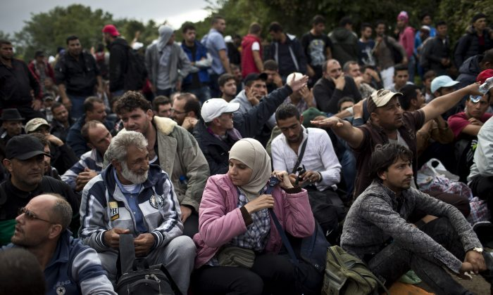 People wait to clear a police line as they entered into Croatia from Serbia, in Babska, Croatia, Friday, Sept. 25, 2015. (AP Photo/Marko Drobnjakovic)