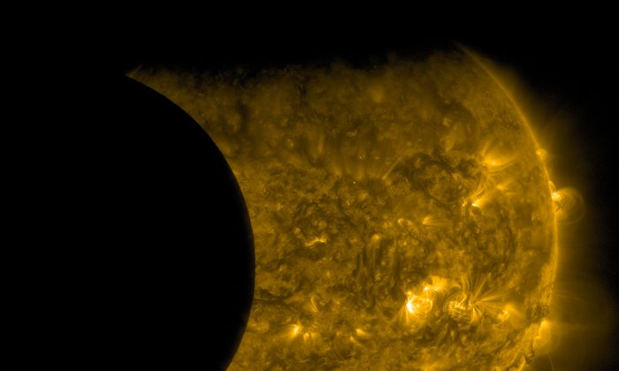 This Sept. 13, 2015 image provided by NASA shows the moon, left, and the Earth, top, transiting the sun together, seen from the Solar Dynamics Observatory.  (NASA/SDO via AP)