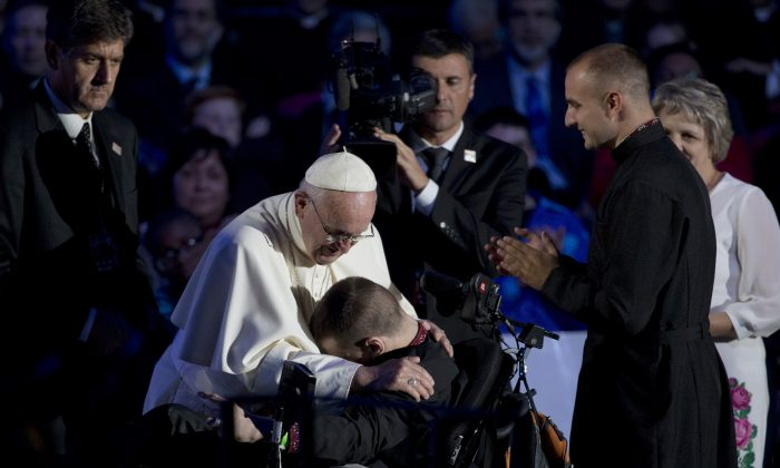Pope Francis embraces a young man in a wheelchair during the World Meeting of Families in the Benjamin Franklin Parkway Saturday, Sept. 26, 2015, in Philadelphia. Hundreds of thousands of Roman Catholics made the pilgrimage to Philadelphia to see Pope Francis on the last leg of his visit to the United States, where they hoped to catch a glimpse of the popular pontiff at some point during his packed schedule — or even receive a blessing or healing touch. (AP Photo/Alessandra Tarantino)