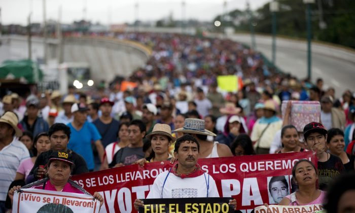 Relatives of the 43 missing Ayotzinapa teachers' college students lead a march marking the one-year anniversary of the students' disappearances in Chilpancingo, Mexico, Saturday, Sept. 26, 2015. (AP Photo/Rebecca Blackwell)