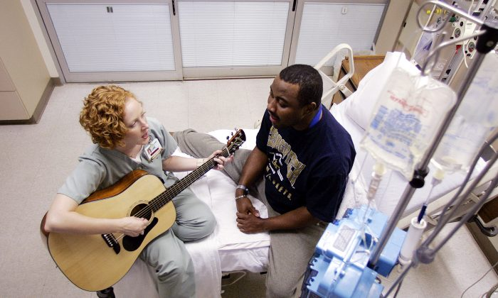 A hospital music therapist  plays her guitar and sings along with a patient at a hospital in Atlanta in this file photo. Music therapy can be deeply emotionally healing. (AP Photo/Dave Martin)