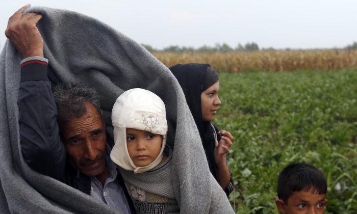 A man protects himself and a child from the rain on no man's land at the Sid border crossing between Serbia and Croatia near Sid, about 100 km west from Belgrade, Serbia, Thursday, Sept. 24, 2015. Tensions escalated between Serbia and Croatia on Thursday as the long-time foes struggled to come up with a coherent way to deal with tens of thousands of migrants streaming through the Balkan nations to seek sanctuary in other parts of Europe. (AP Photo/Darko Vojinovic)