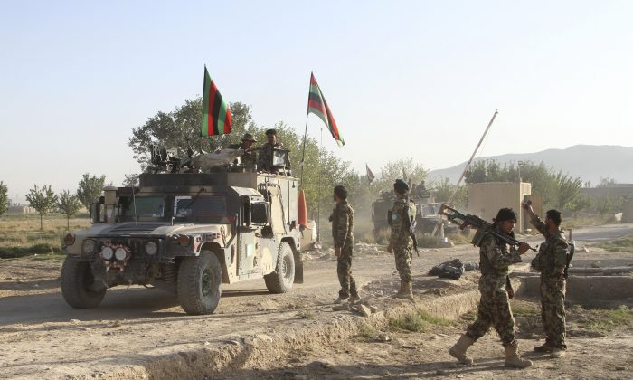 Afghan national army stand guard near the dead body of a Taliban attacker in front of the main prison building after an attack in Ghazni province, eastern Afghanistan, Monday, Sept. 14, 2015. (AP Photo/Rahmatullah Nikzad)