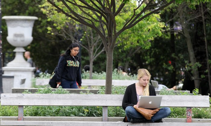 A UC Berkeley student works on her laptop while sitting on the UC Berkeley campus April 23, 2012 in Berkeley, California.  (Justin Sullivan/Getty Images)