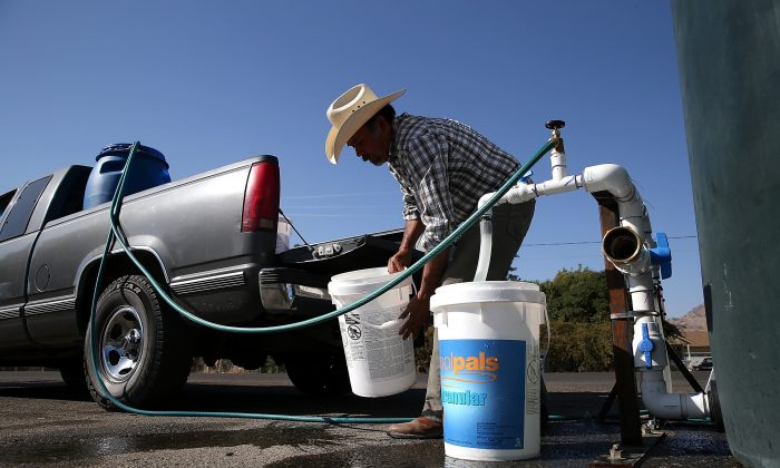 Mario Garcia fills buckets with non-potable water from a tank set up in front of the Doyle Colony Fire Station on September 4, 2014 in Porterville, California. (Justin Sullivan/Getty Images)