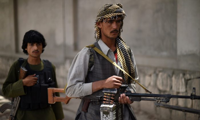 This photograph taken on May 23, 2015, shows Afghan militia forces as they stand with their weapons in Kunduz. (Shah Marai/AFP/Getty Images)