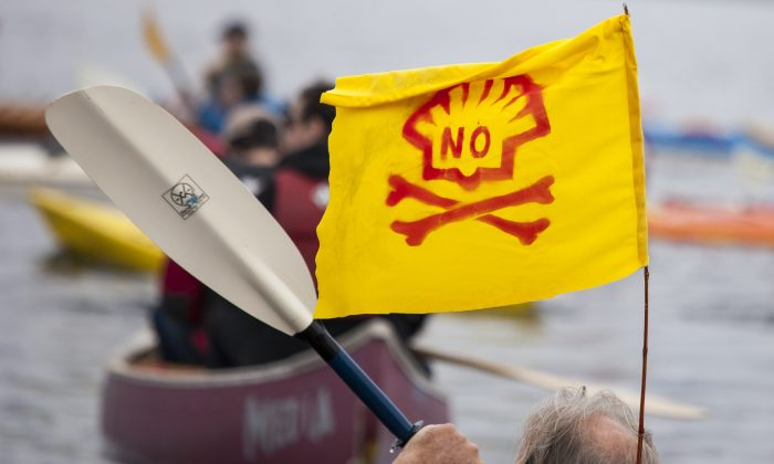 A ShellNo flotilla participant paddles in a kayak with an anti-Shell flag during demonstrations against Royal Dutch Shell on May 16, 2015 in Seattle, Washington. (David Ryder/Getty Images)