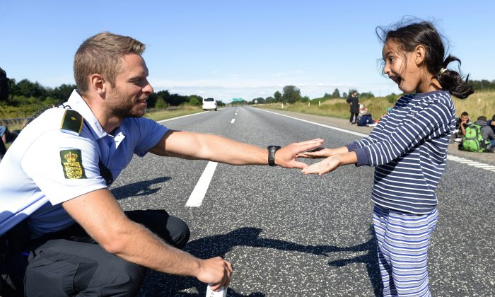 Danish policeman plays with a migrant girl as a group of migrants attempt to walk at the E45 freeway from Padborg, on the Danish-German border, towards Sweden, on September 9, 2015. (CLAUS FISKER/AFP/Getty Images)
