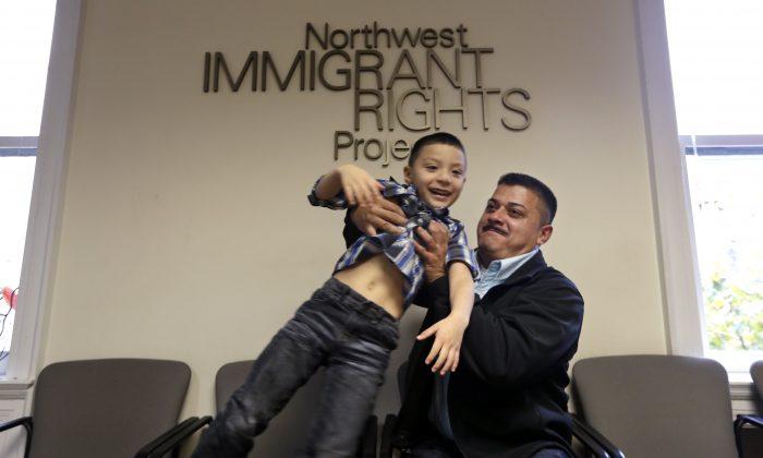 Ignacio Lanuza-Torres playfully lifts his son, Isaiah, 4, as he has his photo taken in Seattle, on Friday, Oct. 17, 2014. (AP Photo/Elaine Thompson)
