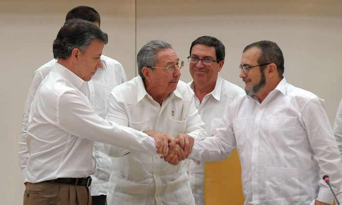 Colombian President Juan Manuel Santos (L) shakes hands with the head of the FARC guerrilla Timoleón Jimenez, aka Timochenko (R), as Cuban President Raúl Castro (C) holds their hands during a meeting in Havana on Sept. 23, 2015. The Colombian government and FARC rebels announced a key breakthrough in their nearly three-year peace talks Wednesday, Sept. 23, with the signing of a deal on justice for crimes committed during the five-decade conflict. The deal includes the creation of special courts and a broad amnesty, though this will not cover 'crimes against humanity, serious war crimes,' and other offenses, including kidnappings, extrajudicial executions, and sexual abuse, said officials from Cuba and Norway, the guarantors in the talks. (Yamil Lage/AFP/Getty Images)