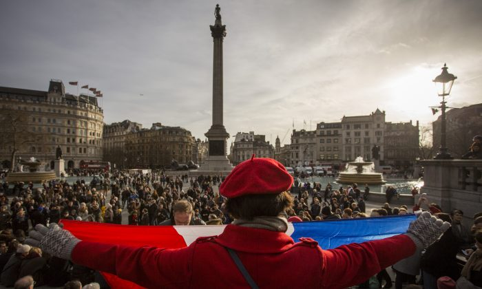 A woman holds the national flag of France as people gather in Trafalgar Square (Rob Stothard/Getty Images)
