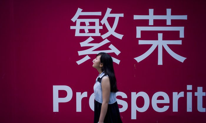 """A woman walks beside a board with the characters for """"prosperity"""" in Chinese in Beijing on July 28, 2015. (FRED DUFOUR/AFP/Getty Images)"""