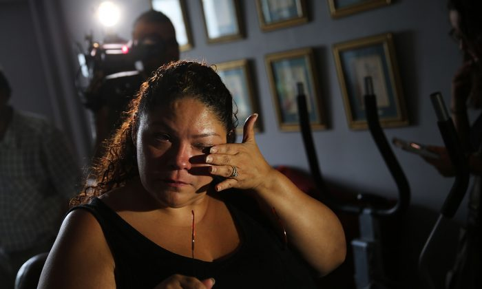 Carmen Ramirez, whose father Carmelo Quiles recently died of Legionnaires disease, pauses in her mothers apartment in an area of the Bronx which is the center of the outbreak on August 6, 2015 in New York City. (Spencer Platt/Getty Images)