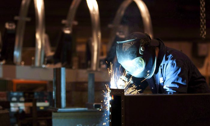 A welder works in a factory in Quebec City in this file photo. Manufacturing advanced 0.6 percent in July. (The Canadian Press/Jacques Boissinot)