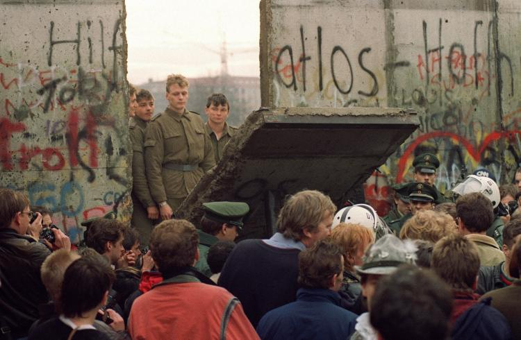 West Berliners crowd in front of the Berlin Wall early 11 Nov. 1989 as they watch East German border guards demolishing a section of the wall in order to open a new crossing point between East and West Berlin, near the Potsdamer Square. (Gerard Malie/AFP/Getty Images)