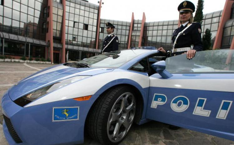 Two Italian police officers showcase the 'Lamborghini Gallardo' police care in Rome on 16 Dec. 2004.  (PATRICK HERTZOG/AFP/Getty Images)