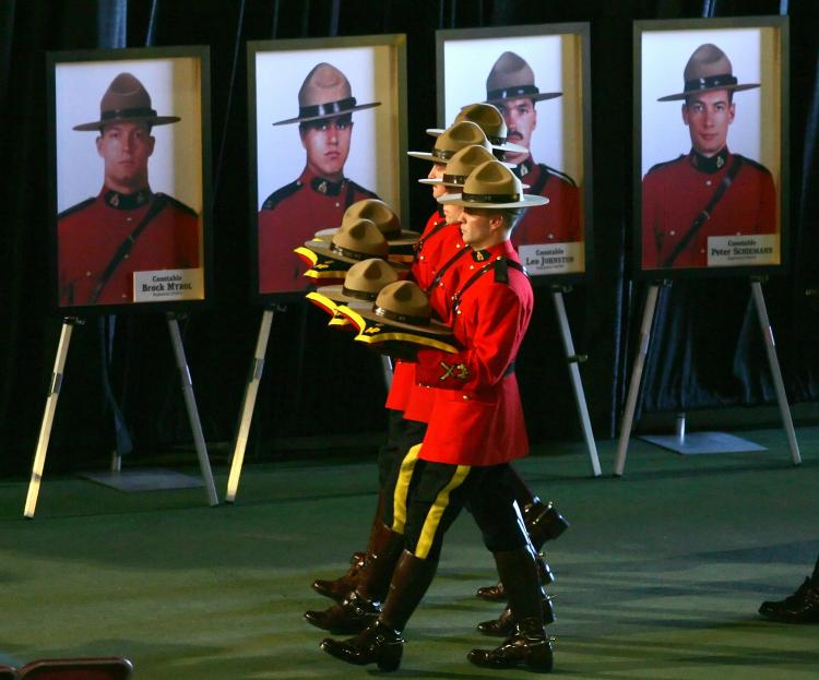 RCMP officers during a memorial service carry the hats of four officers slain in Edmonton in 2005. Two men serving prison sentences for the murders made confessions to Mr. Big operatives.  (Jeff Vinnick/Getty Images)