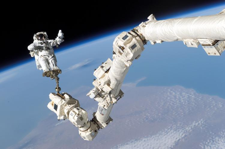 In this NASA handout, mission specialist, Astronaut Stephen K. Robinson, is anchored to a foot restraint on the International Space Station's Canadarm2 robotic arm, during his space walk to repair the underside of the space shuttle Discovery August 3, 2008. (NASA via Getty Images)