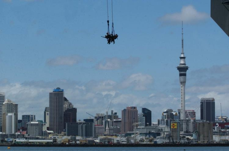 A group of five people roped together jump off Auckland's Harbour Bridge to celebrate 15 years of AJ Hackett bungy jumping in NZ in 2003.  (Phil Walter/Getty Images)