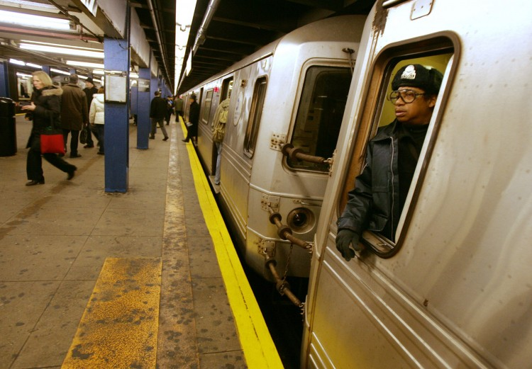 A subway conductor waits for passengers to board the train