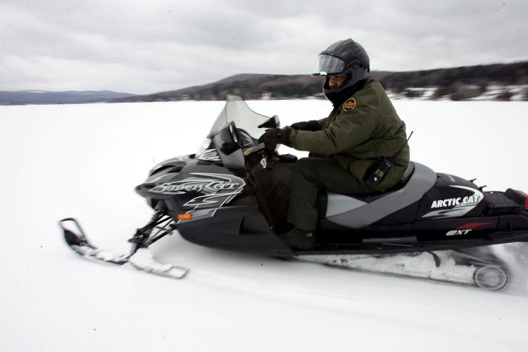 A U.S. Border Patrol agent rides a snowmobile on a frozen lake near the Vermont-Quebec border. (Joe Raedle/Getty Images)