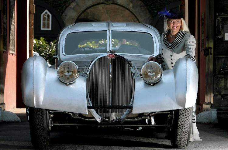 Fair hostesses Sandra poses beside a Bugatti Type 57SC Atlantic car constructed in 1937 to promote the Techno Classica fair, 27 March 2007 in Essen, western Germany. (Volker Hartmann/Getty Images)