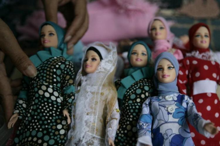 A woman dresses and assembles packaging of 'Arrosa' dolls on July 12, 2007 in Depok, West Java, Indonesia. (Dimas Ardian/Getty Images)