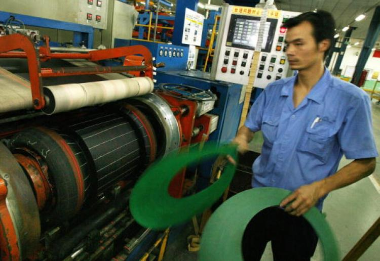 A worker from the Hangzhou Zhongce rubber company pieces together the different sections of a tyre at their factory in Hangzhou, 25 July 2007. (Mark Ralston/AFP/Getty Images)