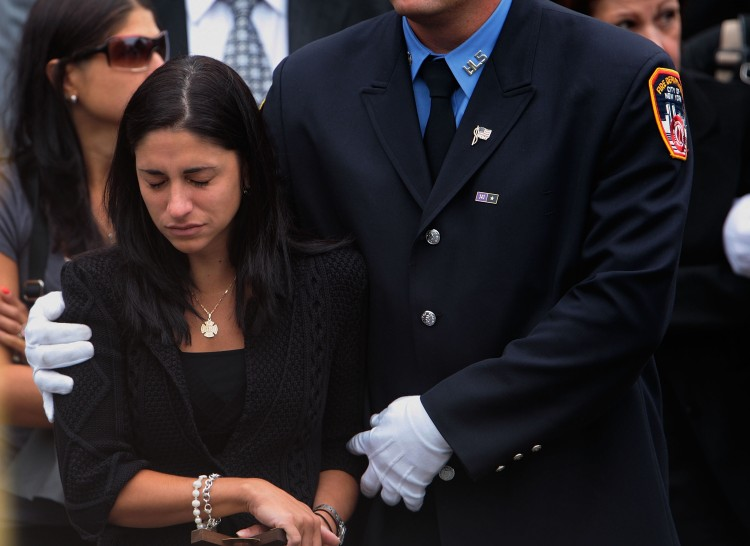 Linda Graffagnino is escorted by a New York firefighter