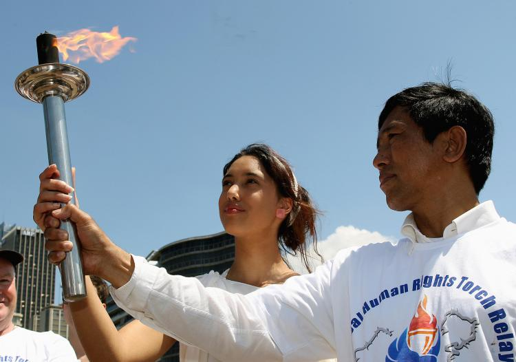 Jameila Douglas (C) and Maung Maung Aye (R), a member of the Burmese Parliament, hold the torch during the Sydney leg of the Global Human Rights Torch Relay.  (Greg Wood/AFP/Getty Images)