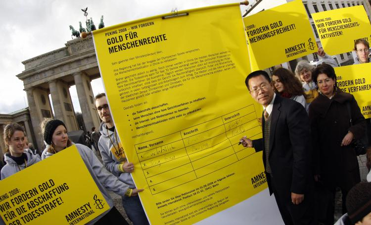 Biao Teng (L) signs a giant petition for human rights in China (Marcus Brandt/AFP/Getty Images)