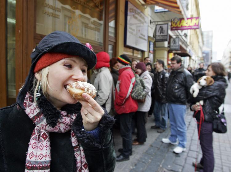 A girl eats a 'paczek,' a popular doughnut like pastry from Poland, as other customers queue in front of a pastry shop in Warsaw on 'Fat Thursday', ahead of the Christian period of Lent last January 2008. (Janek Skarzynski/Getty Images )