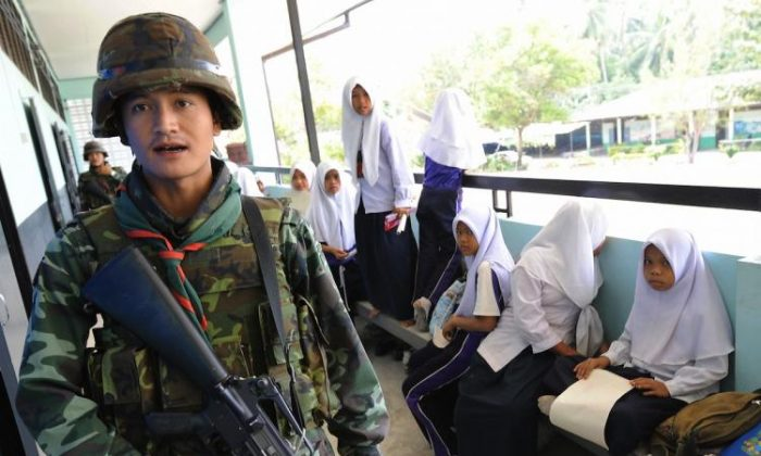 Thai soldiers walk past Muslim students while checking security at a classroom in Pattani Province, southern Thailand. Fourteen government teachers have been killed this year by suspected Muslim insurgents.  (Pornchai Kittiwongsakul/Getty Images )