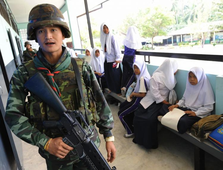 SOLDIERS OCCUPYING SCHOOLS: Thai soldiers walk past Muslim students while checking security at a classroom in Pattani Province, southern Thailand. Fourteen government teachers have been killed this year by suspected Muslim insurgents.  (Pornchai Kittiwongsakul/Getty Images )