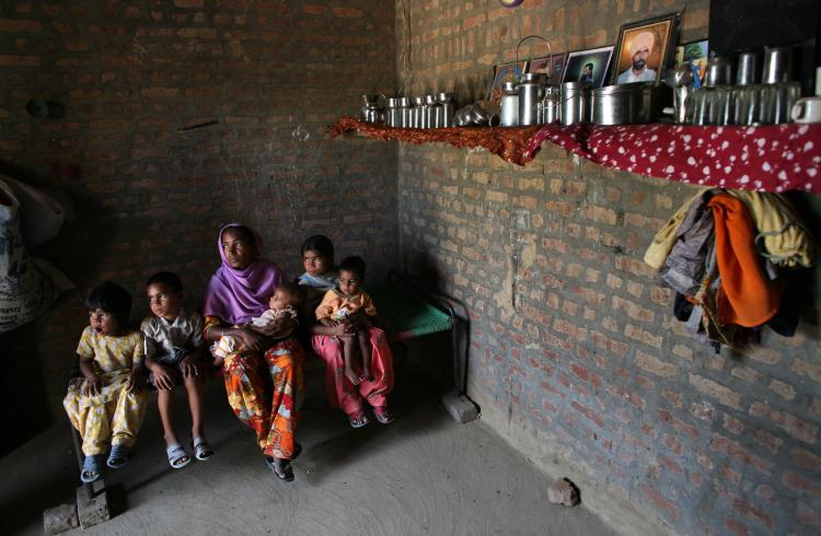 An Indian farmer sits with her children in the village of Bhatuan, 150km west of Chandigarh. Her husband committed suicide in in November 2007 due to debt. (Pedro Ugarte/AFP/Getty Images)