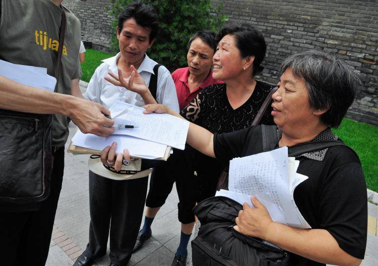 July 2, 2008 Chinese petitioners show their documents listing their grievances to a reporter near a petition office in Beijing. (Teh Eng Koon/AFP/Getty Images)