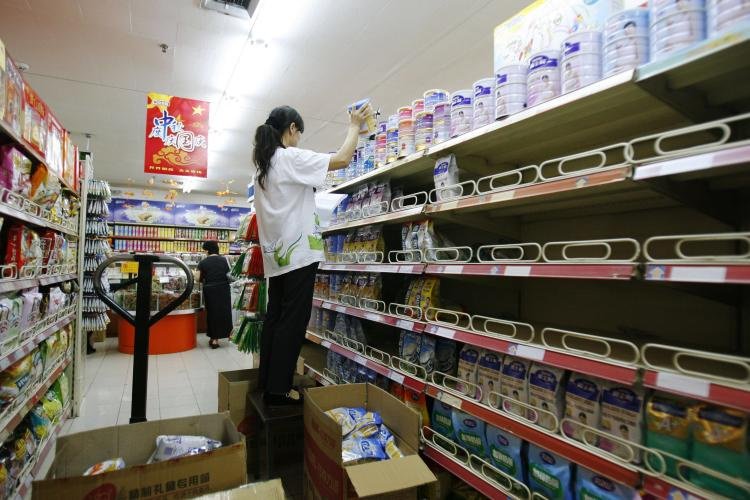 A worker removes melamine-tainted milk powder from the shelf in a supermarket in September in Beijing, China. All the major brands are affected. (China Photos/Getty Images)