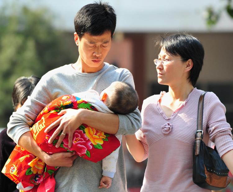 Parents and their baby leave a children's hospital in Beijing on October 16, 2008. Lawyers for victims of China's tainted milk scandal said the government had warned them not to sue.  (Frederic J Brown/AFP/Getty Images)