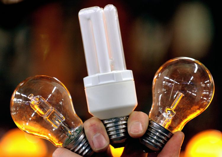 IKEA phases out incandescent light bulbs. Energy-saving light bulbs (C and L) next to an incandescent one (R). (Frederick Florin/AFP/Getty Images)