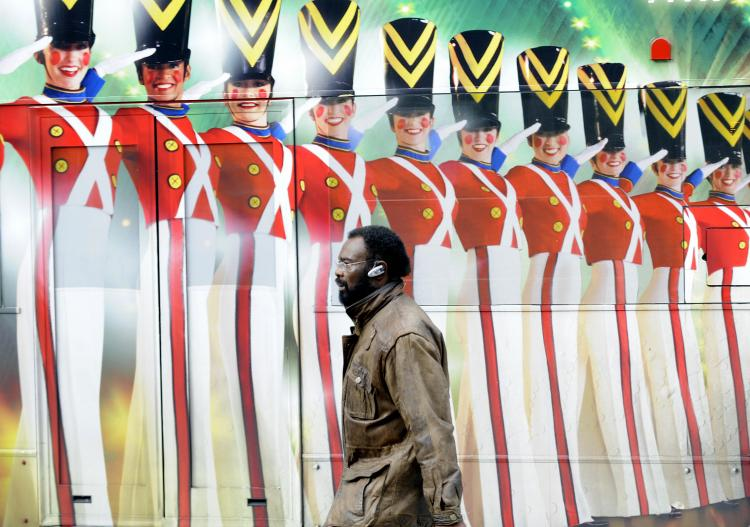 A man walks by a painted advertisement on a side of a bus for Broadway production of the Radio City Christmas Spectacular show, in New York. (Emmanuel Dunand/AFP/Getty Images)