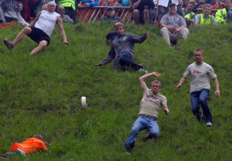 Contestants in the men's race chase a Double Gloucester Cheese down the steep gradient of Cooper's Hill during the annual Bank Holiday tradition of cheese-rolling on May 25, 2009 in Brockworth, Gloucestershire, England.  (Matt Cardy/Getty Images)