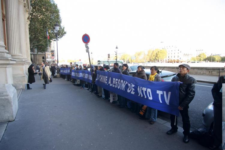 New Tang Dynasty Television (NTDTV) supporters hold banners outside the Paris Commerce Court to support the restoration of NTDTV's broadcast to China. (Ye Xiaobin/The Epoch Times)