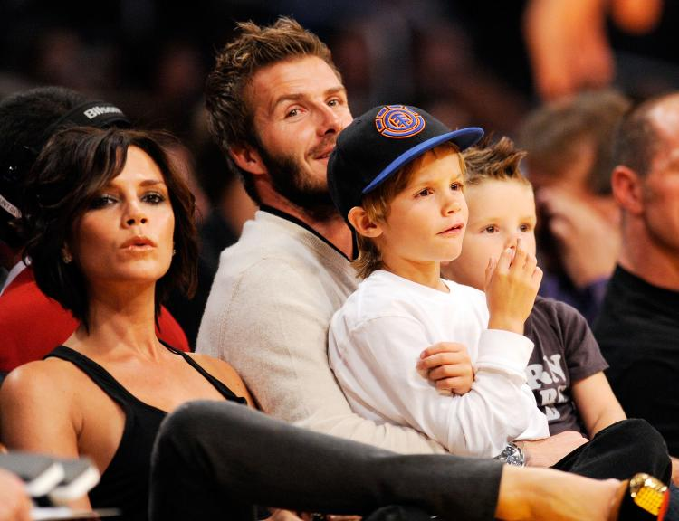 Victoria Beckham, David Beckham, and their boys watch a basketball game between the Los Angeles Lakers and the Dallas Mavericks in Los Angeles in 2009. The Beckhams are expecting their fourth child in summer 2011. (Kevork Djansezian/Getty Images)
