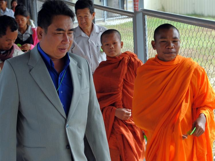 Cambodian Reach Sambath, Chief of the Public Affairs section of the Extraordinary Chambers in the Courts of Cambodia (ECCC), guides monks to attend the trial of former Khmer Rouge prison chief, Kaing Guek Eav (Duch), in Phnom Penh on November 27, 2009. (Tang Chhin Sothy/AFP/Getty Images)