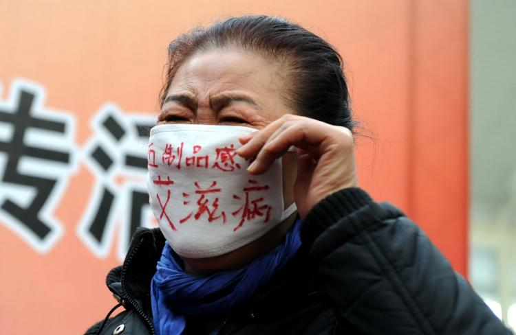 A woman who contracted HIV from infected blood joins a demonstration during an AIDS awareness event on World AIDS Day at Beijing's south railway station in 2009.  (AFP/Getty Images)
