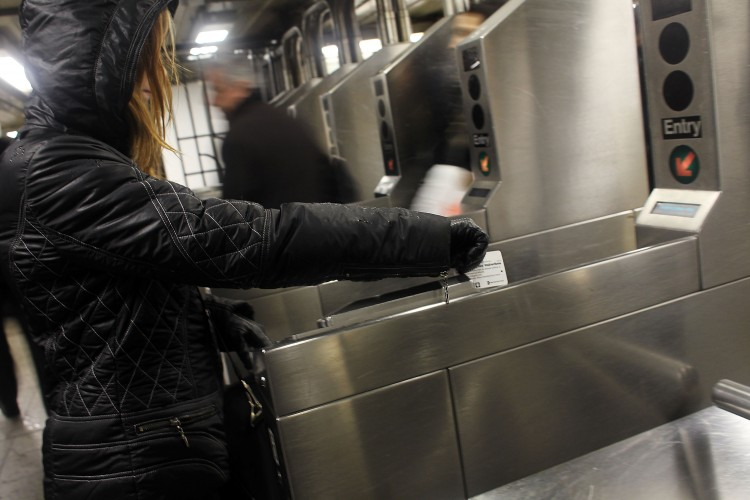 People swipe their metro cards in the New York City subway on February 23, 2010 in New York City. (Spencer Platt/Getty Images)