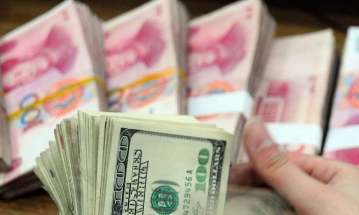 A Chinese bank worker counts a stack of U.S. dollars together with stacks of 100 Chinese yuan notes. China is driving up its national debt to finance its foreign currency reserves, the largest in the world. (STR/AFP/Getty Images)