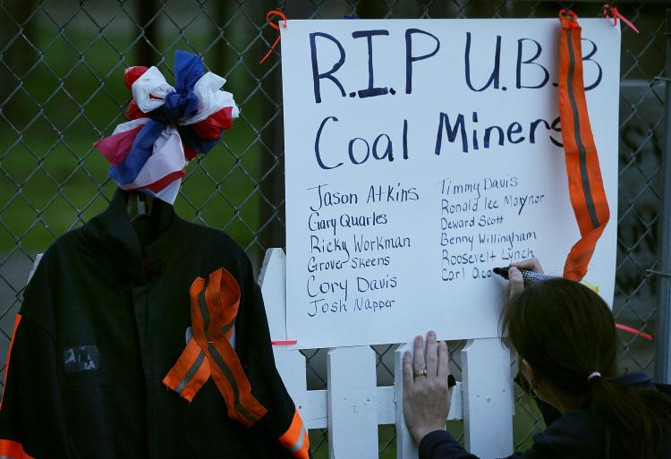 A women writes down the names of 29 fallen coal miners on a small memorial, on April 10, 2010 in Whitesville, West Virginia. On April 5, 29 coal miners were killed during a methane gas explosion at the Massey Energy Company's Upper Big Branch Coal Mine.  (Mark Wilson/Getty Images)