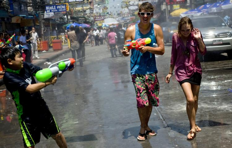 Foreign tourists and a Thai child duel with water guns along a tourist area of Bangkok on April 13 last year during the Songkran festival which marks the Thai New Year. (Manpreet Romana/AFP/Getty Images)