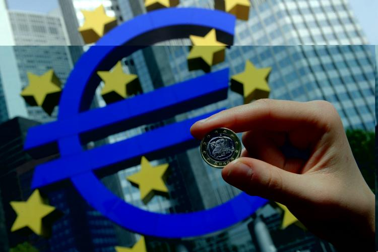 A woman poses with a euro coin in front of the giant symbol of the EU's currency outside the European Central Bank's headquarters in Frankfurt, Germany, on April 29. The euro has slipped in recent weeks against the U.S. dollar due to Europe's sovereign debt woes.(Thomas Lohnes/AFP/Getty Images )